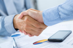 Close Up Of Businesspeople Shaking Hands At Desk